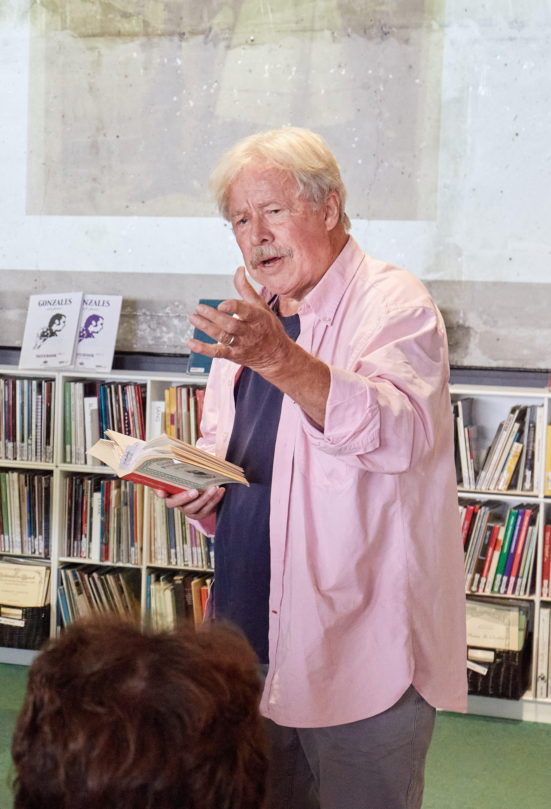 """Sven Wollter på scenen på Stockholms kulturhus. I handen håller han pocketboken """"Gustaf Frödings samlade poesi."""""""